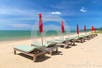 Solstolar på den tropiska stranden