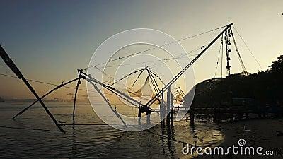 Soluppgång över kinesiska fisknät och fartyget i Cochin, Indien lager videofilmer