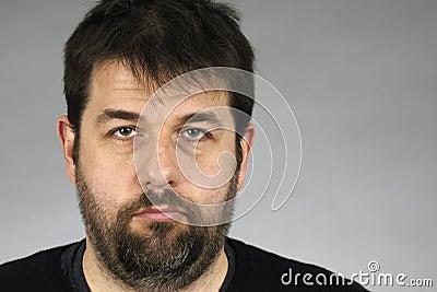 Somber bearded man over grey