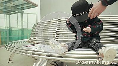 Sombrero cae sobre la cabeza roja de una niña que está sentada en un banco con galleta metrajes