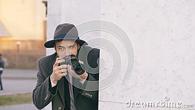 Sombrero que lleva y capa del agente masculino joven del espía que fotografían a gente criminal y que ocultan detrás de la pared almacen de video