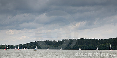 Some yachts sailing under stormy sky