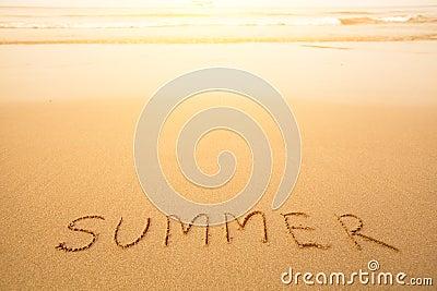 Sommar - skriftlig text räcker by i sand på en strand