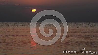 Sommarsol bak moln, ovanför havet, med försiktig reflexion stock video