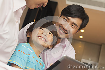Son and his parents using digital tablet