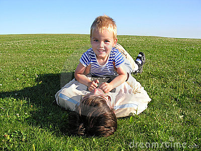 Son lie on father on green grass 2