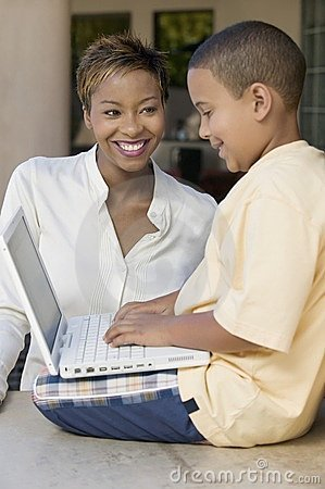 Son and mother in living room using laptop