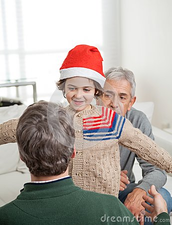 Son In Santa Hat About To Embrace Father