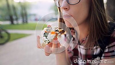Sonderkommando der Frau die geschmackvolle Pizza essend im Freien in der Straße stock footage