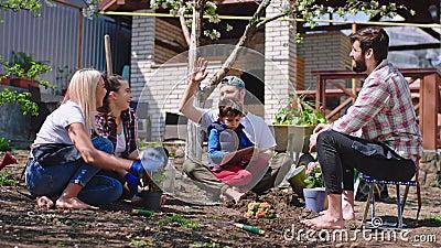Sonnentag für eine Gruppe von Freunden im Garten, die sich ein paar Blumen anpflanzen und sich glücklich und entspannt fühlen. stock video