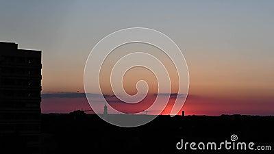 Sonnenuntergang auf einem fast klaren Himmel in München, Deutschland Silhouetten von Häusern, einer Kirche und einem stock footage