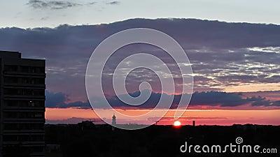 Sonnenuntergang mit vielen Wolken und Wolken am Himmel in München, Deutschland Silhouetten von Häusern, einer Kirche und einem stock footage