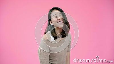 Sonriendo adorable mujer asiática con expresión positiva, sonríe ampliamente, vestida con ropa informal y mirando a la cámara almacen de metraje de vídeo