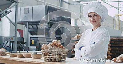 Sonrisa grande comercial del panadero atractivo de la mujer en un sector panadero que mira derecho de llevar del primer de la cám almacen de metraje de vídeo