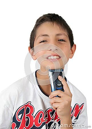 Sonrisas dentudas del muchacho y barbilla el afeitar con la máquina de afeitar