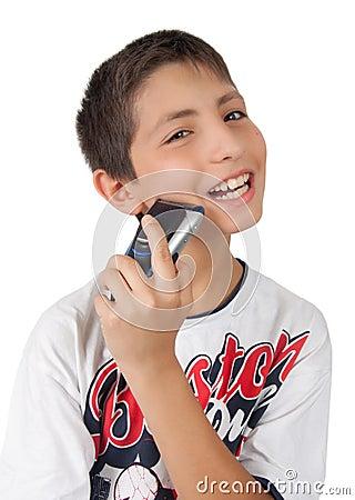 Sonrisas dentudas del muchacho y mejilla el afeitar con la máquina de afeitar