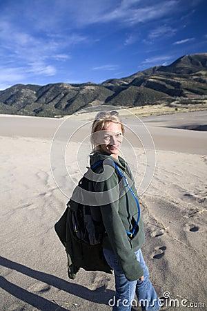 Sorridere facendo un escursione donna sulla sabbia