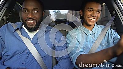 Sorriso de pai americano elogiando filho aprendendo a dirigir auto, ajuda dos pais, família filme