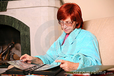 Sorrow senior woman at home holding a photoes