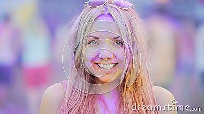 Sourire sincère de la jeune femme gaie ayant l'amusement au festival passionnant de couleur banque de vidéos