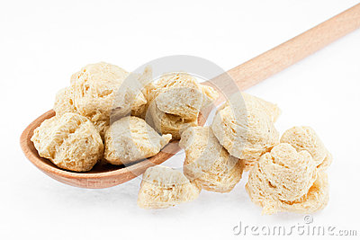 Soya flakes in wooden spoon on white background