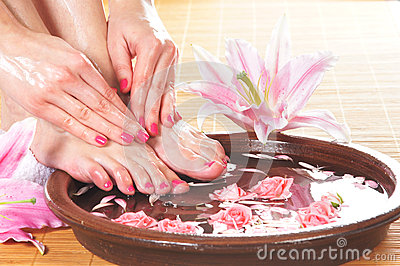 A spa composition of feet and petals in a bowl