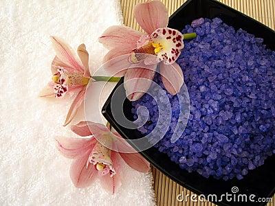 Spa essentials (violet salt, white towel and pink orchids)