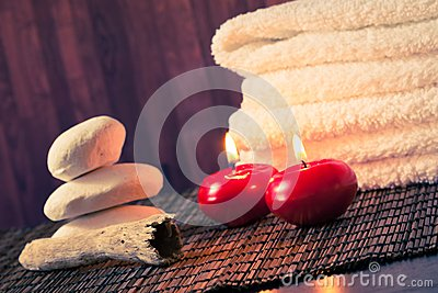 Spa massage border background with towel stacked stone and red candles warm atmosphere