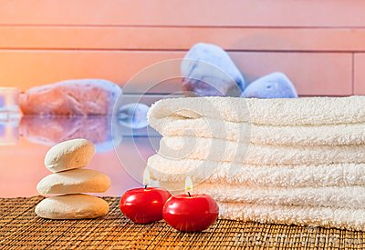 Spa massage border with towel stacked,red candles near stone