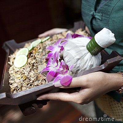 Spa massage setting with thai herbal compress stamps on woman ha