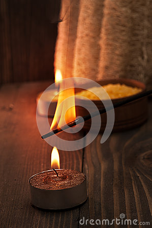 Spa setting with candle and aroma stick on wooden background