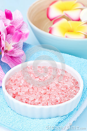 Spa setting with with sea salt and pink flowers, vertical