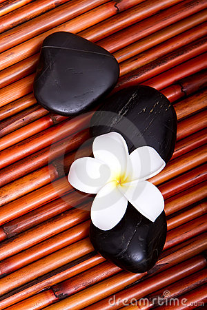 Spa stones and frangipani flower on bamboo