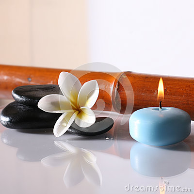 Spa stones and lit candle
