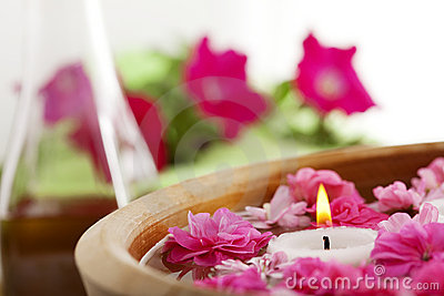Spa therapy, flowers in water, on a bamboo mat.
