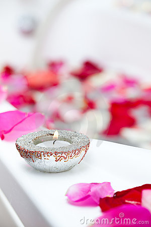 Spa treatment bathtub with petals and candles