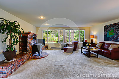 Spacious living room with brick wall trim and stove
