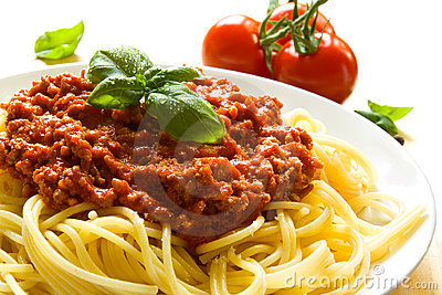 Plate of spaghetti bolognese with ingredients in the background