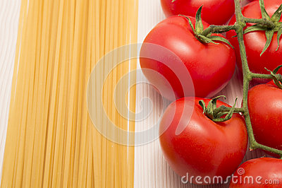 Spaghetti and tomatoes on a table ready to cook