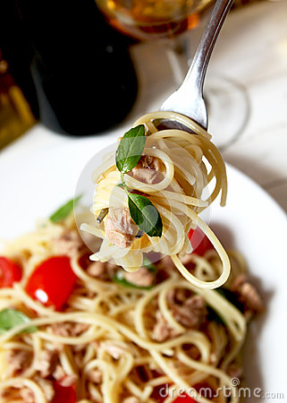 Spaghetti with tuna fish and basil in a fork