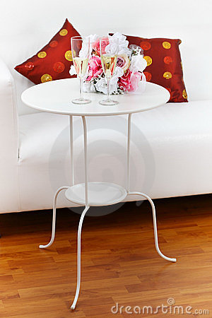 Sparkling wine with bouquet on side table
