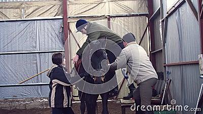 In speciale hangaar, leert een jongelui gehandicapte mens, met kunstmatig lidmaat om een paard met dichte supervisieleraren te be stock video