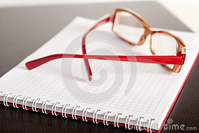 Spectacles and a notepad
