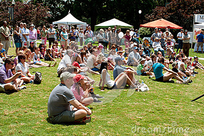 Spectators Sitting On Grass Watch Performance At Festival Editorial Stock Photo