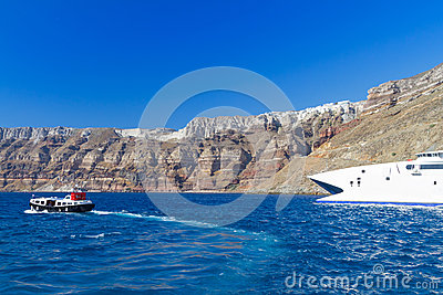 Speedboat at high volcanic cliff of Santorini island