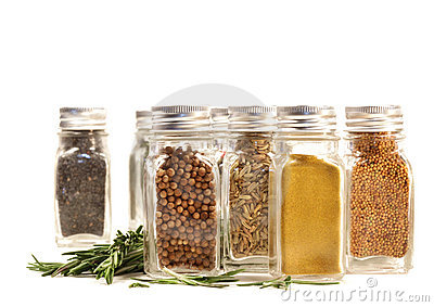 Spice jars with fresh rosemary leaves against white
