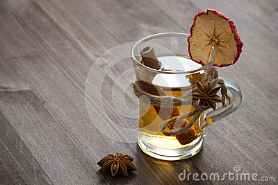 Spiced apple cider in glass mug on a wooden table