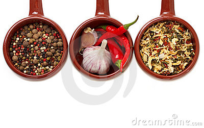 Spices and garlic in ceramic bowls.