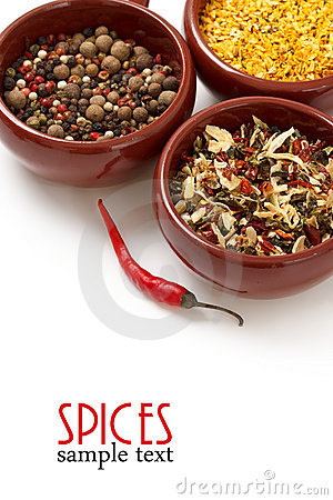Spices and herbs in ceramic bowls.