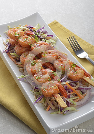 Spicy shrimp skewers on coleslaw salad